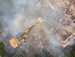 Aerial view of excavator destroys a building