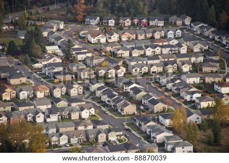 Aerial view of family homes on the hillside at sunset - stock photo