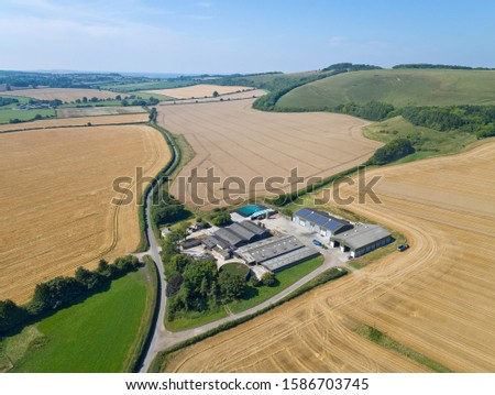 Aerial View Of Farm Buildings Surrounded By Fields Of Wheat