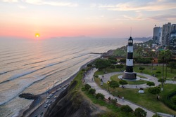 Aerial view of Faro la Marina located in Miraflores's park by the ocean in Lima, Peru. People, tourists and cyclists having fun in