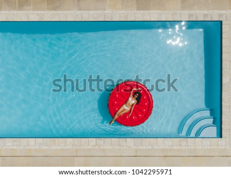 Aerial view of female lying on inflatable mattress in the pool. Relaxed woman floating on inflatable mattress in swimming pool.