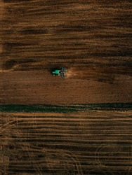 Aerial view of field in which tractor plows.Blue tillage equipment and green tractor are clearly visible on dark brown background of earth with drawings from tillage and wheels and green grassy line.