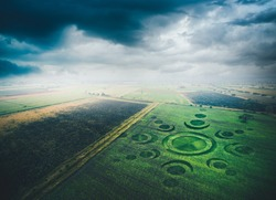 Aerial view of fields with an alien crop circle formation / photo composite