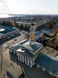 Aerial view of Fire Tower Kostroma city, Russia. Cityscape, orthodox temple, houses on background. Russian old historical town. Spring, sunny day, street with going cars, bare trees