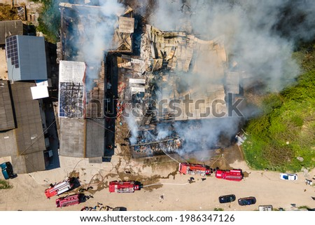 Aerial view of firefighters extinguishing ruined building on fire with collapsed roof and rising dark smoke. Stock photo ©