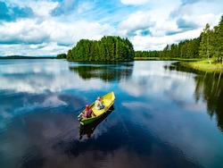 Aerial view of fishing boat with young woman and man in blue summer lake in Finland