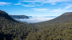 Aerial view of fog in Megalong Valley near Blackheath in The Blue Mountains in regional New South Wales in Australia
