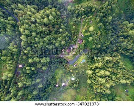 aerial view of forest, cabbin and pool