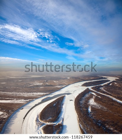 Aerial view of forest of plain and small river during a winter day.