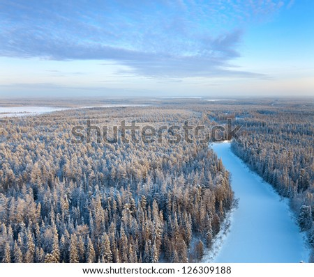 Aerial view of forest river during winter day.