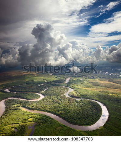 Aerial view of forest the river during summer day on background of great white clouds.