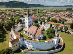 Aerial view of fortified church surrounded powerful thick walls in Transylvania overlooking the village in a beautiful summer day. Romania.