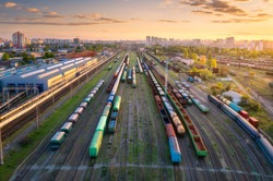 Aerial view of freight trains at sunset. Top view of railway station, wagons, railroad. Heavy industry. Industrial landscape with train in depot, city, buildings, colorful sky. Transportation