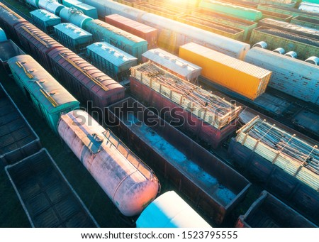 Photo of  Aerial view of freight trains. Colorful cargo wagons on railway station. Wagons with goods on railroad. Heavy industry. Industrial landscape with train, railway platfform at sunset. Top view. Depot