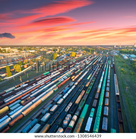 Aerial view of freight trains on railway station at colorful sunset. Wagons with goods on railroad. Heavy industry. Industrial. Cargo trains, city buildings and orange sky with red clouds. Top view