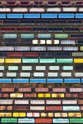 Aerial view of freight trains on the railway station. Cargo trains close-up. Wagons with goods on railroad. Industrial conceptual scene with trains. Top view.