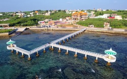 Aerial view of gazebos standing over blue seawater on a sunny summer day and connected by a bridge to the shore with a temple located in the village, in Xiaochijiao, Xiyu Township, Penghu, Taiwan