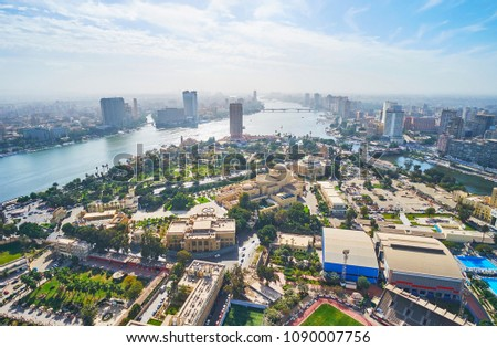 Aerial view of Gezira Island with Opera House and museums and the banks of Nile river with dense housing of Cairo and Giza, Egypt.
