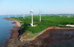 Aerial view of giant wind turbines standing in the green field by the beach in a seaside park along the beautiful coastline on a sunny summer day, in Zhongtun, Baisha Township, Penghu County, Taiwan