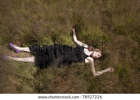 Aerial view of girl in long dress lying on her back in field of long grass