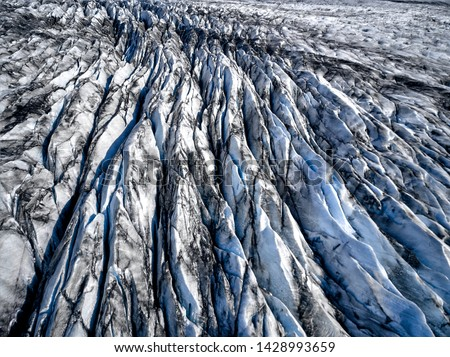 Aerial view of glacier from above, ice and ashes of the volcano texture landscape, beautiful nature ice background from Iceland #1428993659