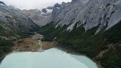 Aerial view of glacier water Emerald Lake in Ushuaia, Tierra del Fuego, Patagonia Argentina. Turquoise water lake in the Andes mountaintop surrounded by rocky mountain peaks and forrest.