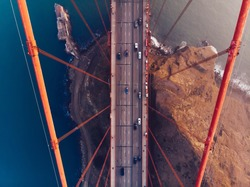 Aerial view of Golden Gate Bridge in foggy visibility during evening time, metropolitan transportation  infrastructure, birds eye view of automotive car vehicles on road of suspension construction