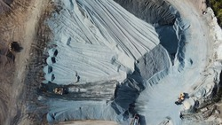 Aerial view of gravel quarry and professional excavators at work. Stock footage. Top view of industrial landscape after stone mining, construction industry.
