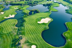 Aerial view of green grass and trees on a golf field.