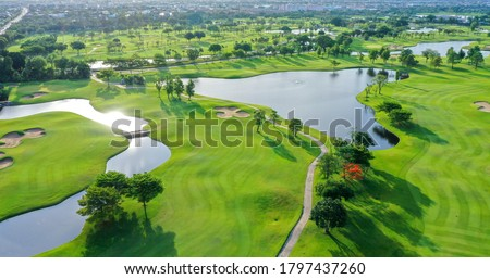 Aerial view of green grass and trees on a golf field, fairway and putting green top view, Bangkok Thailand. bird view over Golf course in the tropical Bangkok.
