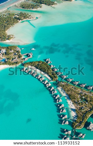 Aerial view of green water and bungalows