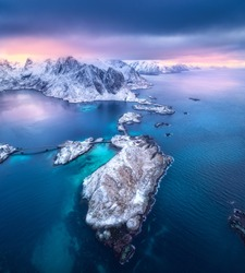 Aerial view of Hamnoy at dramatic sunset in winter in Lofoten islands, Norway. Landscape with blue sea, snowy mountains, rocks and islands, village, buildings, road, bridge, cloudy pink sky. Top view