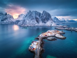 Aerial view of Hamnoy at dramatic sunset in winter in Lofoten islands, Norway. Moody landscape with blue sea, snowy mountains, rocks, village, buildings, rorbu, road, bridge, cloudy sky. Top view
