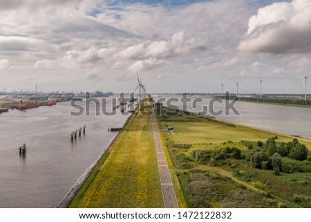 Aerial view of headland, split of land turning into a dyke at Rozenburg, Holland.  Spontaneous green development in the Rotterdam port area. Windmills, sea vessels, oil refineries storm surge barrier Stockfoto ©