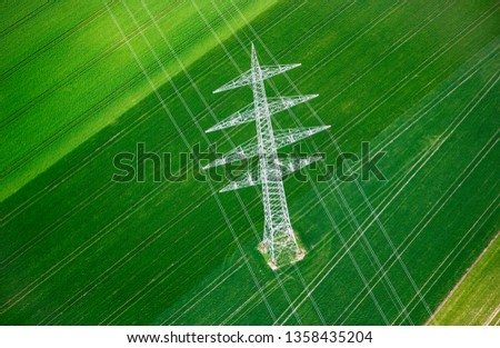 Aerial View of High Voltage Post or High Voltage Tower in Agriculture Field. Aerial Photography / Shot of High Voltage Electricity Tower on Green Field.