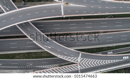 Aerial view of highway and overpass in city on a cloudy day #1015474663