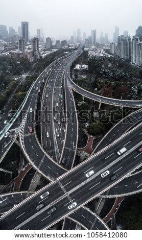 Aerial view of highway and overpass in city on a snowy day #1058412080
