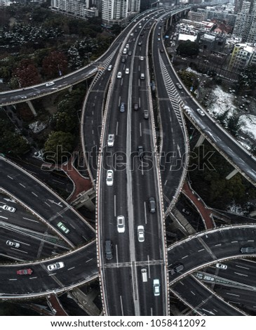 Aerial view of highway and overpass in city on a snowy day #1058412092