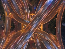 Aerial view of highway junctions shape letter x cross at night with fog. Bridges, roads, or streets in transportation concept. Structure shapes of architecture in urban city, Shanghai Downtown, China.