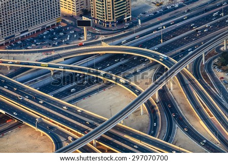 Aerial view of highway road intersections with traffic in a big city (Dubai) at sunset. Transportation concept.