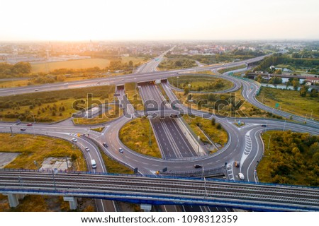 Aerial view of highway road junction at sunset. Highways, railway and green fields on the outskirts of the city. Transport concept. #1098312359