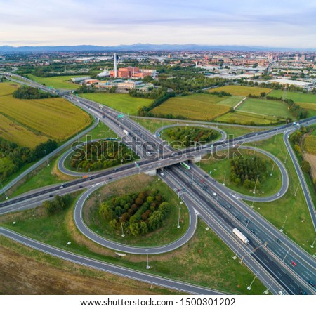 Aerial view of highway road junction. Highways, railway and green fields on the outskirts of the city. Cars and trucks traffic. Transport concept. #1500301202