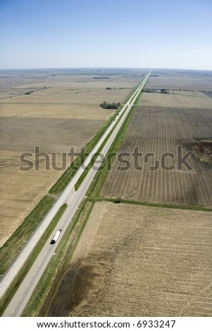 Aerial view of highway through rural farmland with crops.