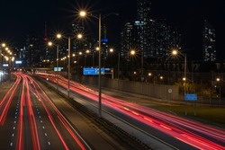 Aerial view of highway with fast moving cars creating long light trails, city skyline in the background. High travel speed effect, dui, dangerous, careless, stunt, drunk driving concept. Long exposure
