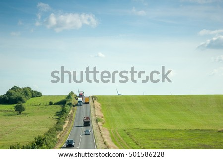 Aerial view of highway with two lane wih cars, trucks adn motorcycles driving between green fields and wind mills behind the hills