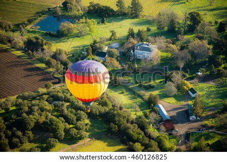 Aerial view of hot air balloon flying over green Napa valley / vineyards / houses on a sunny day