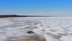 Aerial view of hovercraft riding on snow-covered ice of lake in winter. Drone view of modern airboat moving across frozen river or lake