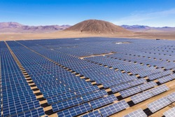 Aerial view of hundreds solar energy modules or panels rows along the dry lands at Atacama Desert, Chile. Huge Photovoltaic PV Plant in the middle of the desert from an aerial drone point of view