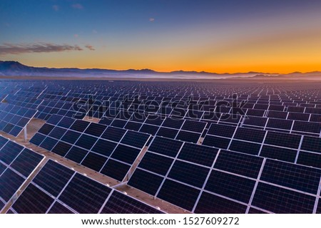 Aerial view of hundreds solar energy  panels rows along the dry lands at Atacama Desert, Chile. Huge Photovoltaic PV Plant in the middle of the desert from an aerial drone point of view during sunset