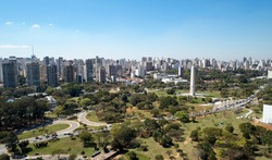 Aerial view of Ibirapuera park in Sao Paulo city, obelisk monument. Prevervetion area with trees and green area of Ibirapuera park. Office buildings and apartments in the background on a sunny day.